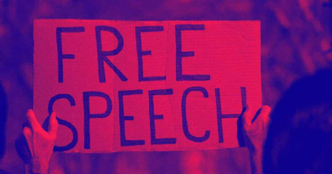 "A protester holds a sign that says, ""Free Speech."""