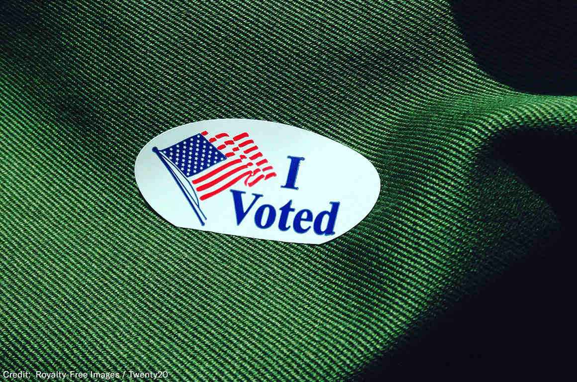 "Photo of a sticker that says ""I voted"" with a waving American flag"