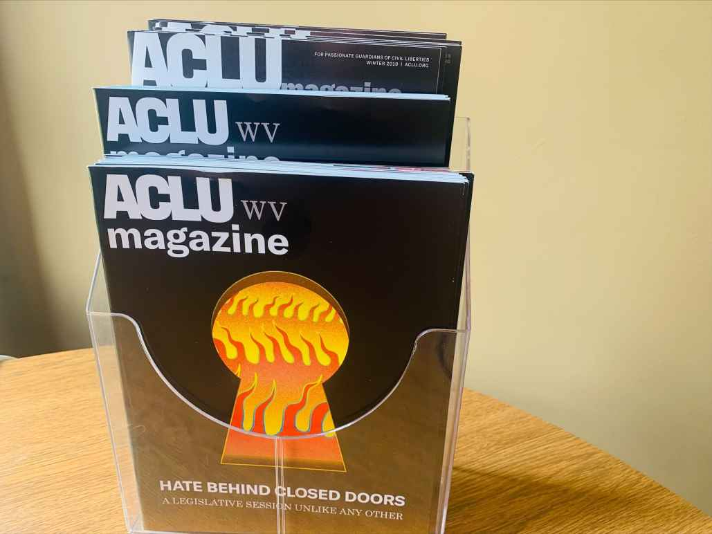 2021 ACLU-WV Magazine cover features image of flames seen through a keyhole with the words: Hate Behind Closed Doors