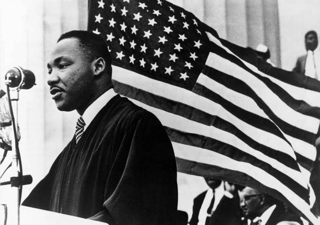 Black and White Photo shows Dr. Martin Luther King Jr. in front of an American flag