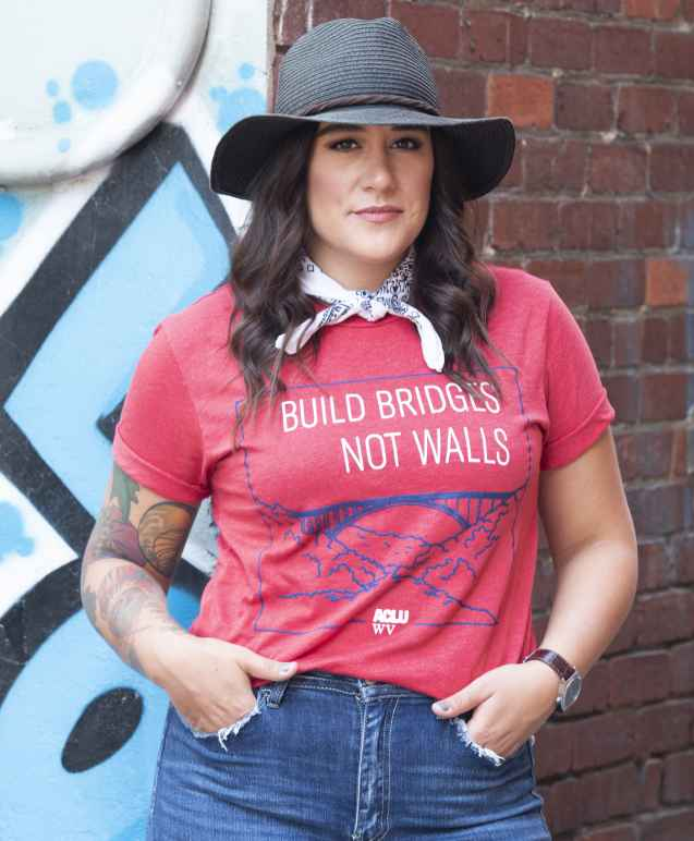 Model is pictured wearing a red Build Bridges Not Walls Tee Shirt showing the New river Gorge Bridge